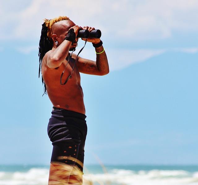 Mand på strand med kikkert